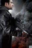 Hombre con la chaqueta de cuero y el rifle de asalto largos fotografía de archivo libre de regalías