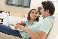 Hombre con la chica joven en sala de estar con la computadora portátil