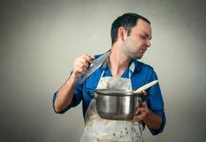 Hombre con la comida en cacerola y mún olor fotos de archivo libres de regalías