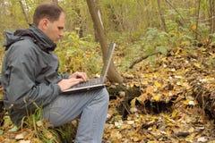 Hombre con la computadora portátil al aire libre Fotos de archivo