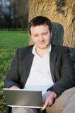 Hombre con la computadora portátil bajo un árbol Fotos de archivo libres de regalías