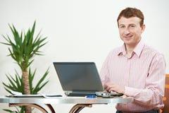 Hombre con la computadora portátil del ordenador en oficina Fotos de archivo libres de regalías