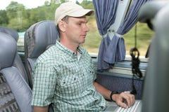 Hombre con la computadora portátil en el omnibus Foto de archivo libre de regalías