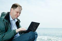 Hombre con la computadora portátil en la playa Imagenes de archivo