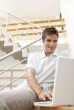 Hombre con la computadora portátil en la sonrisa de las escaleras Imagenes de archivo