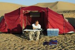 Hombre con la computadora portátil y el cargador solar portable Imagen de archivo libre de regalías