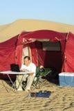 Hombre con la computadora portátil y el cargador solar portable Imágenes de archivo libres de regalías
