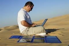 Hombre con la computadora portátil y el cargador solar portable Fotografía de archivo