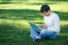 Hombre con la computadora portátil y el teléfono celular al aire libre Fotos de archivo libres de regalías