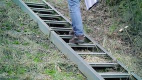 Hombre con la documentación que camina las escaleras para arriba metrajes