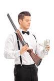 Hombre con la escopeta que cuenta el dinero Foto de archivo libre de regalías