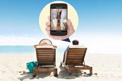 Hombre con la esposa que mira el sistema de seguridad en el teléfono móvil Fotos de archivo libres de regalías