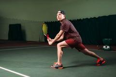 Hombre con la estafa de tenis que juega en corte interior Imágenes de archivo libres de regalías