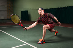Hombre con la estafa de tenis que juega en corte interior Fotografía de archivo