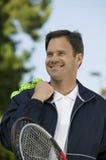 Hombre con la estafa de tenis y las pelotas de tenis Fotografía de archivo libre de regalías