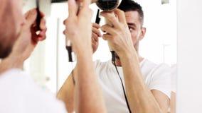Hombre con la fan que se seca el pelo en el cuarto de baño almacen de video