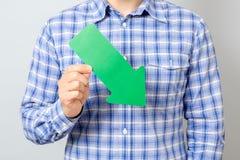 Hombre con la flecha verde que señala a la derecha y abajo Imagen de archivo libre de regalías