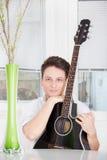 Hombre con la guitarra en casa Foto de archivo libre de regalías
