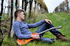Hombre con la guitarra en viñedo Foto de archivo
