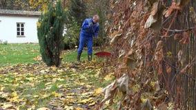 Hombre con la herramienta del rastrillo que rastrilla las hojas afuera en día frío de la caída en yarda de la casa 4K metrajes
