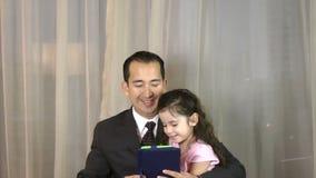 Hombre con la hija que juega con la tableta digital metrajes