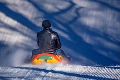 Hombre con la hija sledding abajo de una colina nevosa imágenes de archivo libres de regalías