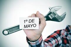 Hombre con la llave ajustable y letrero con el texto 1o de Mayo, m Imagen de archivo libre de regalías