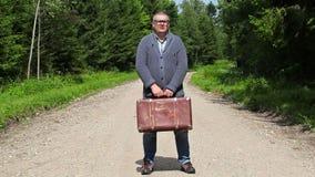 Hombre con la maleta en el camino rural en bosque almacen de video