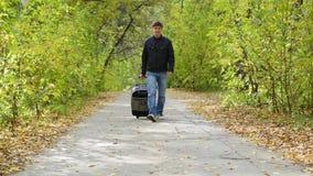 Hombre con la maleta que camina en el pavimento almacen de video