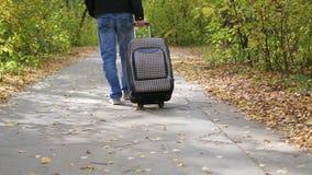 Hombre con la maleta que camina en el pavimento metrajes