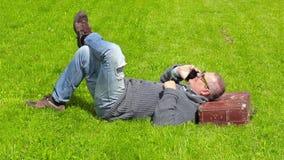 Hombre con la maleta que duerme en hierba y que habla en el teléfono elegante almacen de video