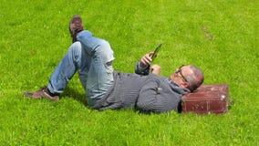Hombre con la maleta que duerme en hierba y que usa la tableta metrajes