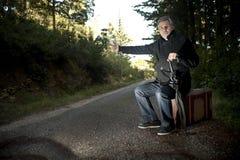 Hombre con la maleta que hace autostop en un camino rural Foto de archivo libre de regalías
