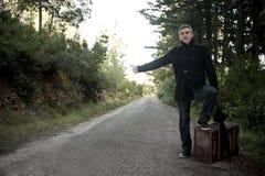 Hombre con la maleta que hace autostop en un camino rural Foto de archivo