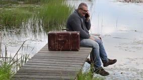 Hombre con la maleta que se sienta cerca del lago y que habla en el teléfono metrajes