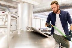 Hombre con la manguera que trabaja en la caldera de la cervecería de la cerveza del arte imagen de archivo