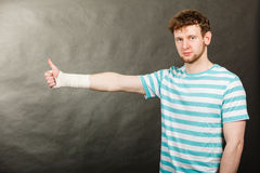 Hombre con la mano vendada que muestra el pulgar para arriba Foto de archivo