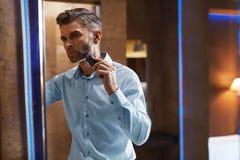 Hombre con la maquinilla de afeitar eléctrica que afeita la cara en cuarto de baño Preparación de los hombres Fotos de archivo libres de regalías