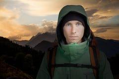 Hombre con la mochila en el fondo de la puesta del sol de la montaña El ir de excursión Imagenes de archivo