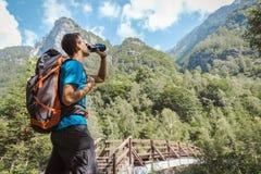 Hombre con la mochila que bebe de la botella de agua rodeada por la naturaleza asombrosa imagen de archivo libre de regalías