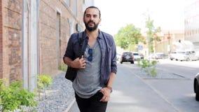 Hombre con la mochila que camina a lo largo de la calle 19 de la ciudad metrajes