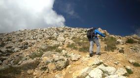 Hombre con la mochila que camina y que sube las rocas, alcanzando el top del pico de Oshten Tirado en la cámara lenta almacen de video