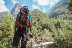 Hombre con la mochila que comtempla su meta siguiente rodeado por la naturaleza y las montañas asombrosas imágenes de archivo libres de regalías