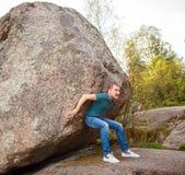 Hombre con la mochila que empuja una piedra enorme Foto de archivo
