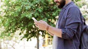 Hombre con la mochila que manda un SMS en smartphone en la ciudad 47 almacen de metraje de vídeo