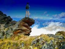 Hombre con la mochila que se coloca en un acantilado que disfruta de una visión al valle en paisaje escénico de la montaña imagen de archivo