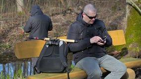 Hombre con la mochila y la caña de pescar que se sientan en el banco y que usan la tableta almacen de video