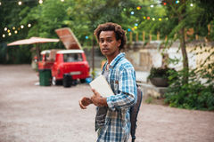 Hombre con la mochila y los libros que camina en el parque Imágenes de archivo libres de regalías