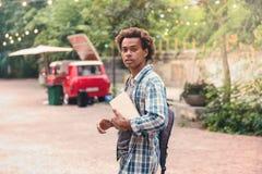 Hombre con la mochila y los libros que camina en el parque Fotografía de archivo