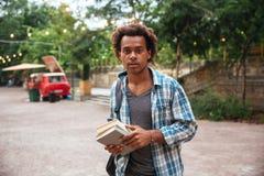 Hombre con la mochila y los libros que se colocan en el parque Imágenes de archivo libres de regalías